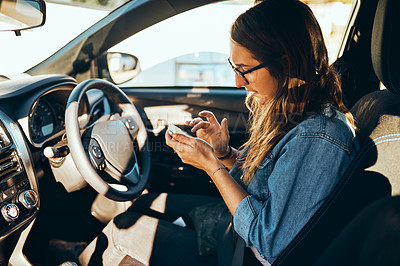 Buy stock photo Cropped shot of an attractive young woman sending a text message while sitting in her car