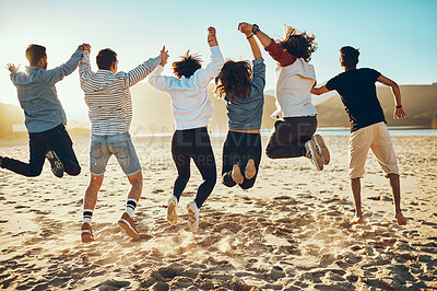 Buy stock photo Rearview shot of a group of unrecognizable young friends jumping with their arms raised on the beach