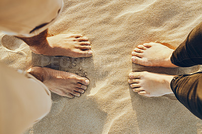Buy stock photo High angle shot of an unrecognizable young couple standing barefoot in the sand at the beach