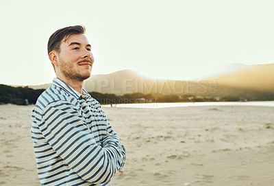 Buy stock photo Cropped shot of a handsome young man standing with his arms folded on the beach