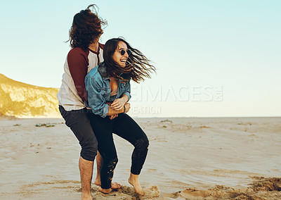 Buy stock photo Full length shot of an affectionate young couple messing around while enjoying their day at the beach