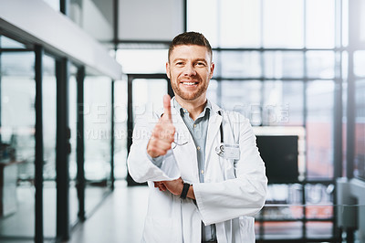 Buy stock photo Portrait of a mature doctor showing thumbs up in a hospital