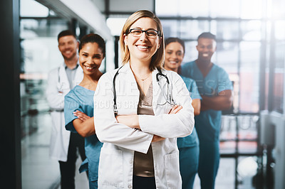 Buy stock photo Portrait of a doctor standing in a hospital with her colleagues in the background