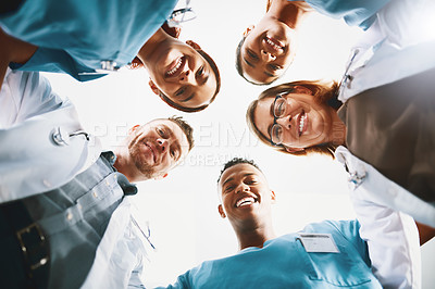 Buy stock photo Low angle shot of a group of medical practitioners standing together in a huddle