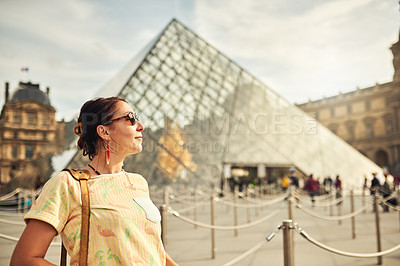 Buy stock photo Cropped shot of an attractive young woman exploring the city of Paris in France with the Louvre in the background