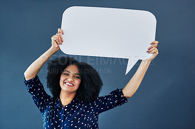 Buy stock photo Studio shot of a young woman holding up a blank speech bubble against a blue background