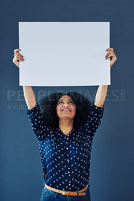 Buy stock photo Studio shot of a young woman holding up a blank placard against a blue background