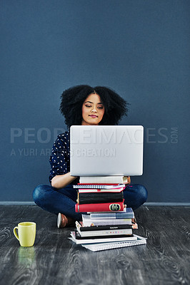 Buy stock photo Studio shot of a young woman using a laptop with books stacked in front of her against a blue background