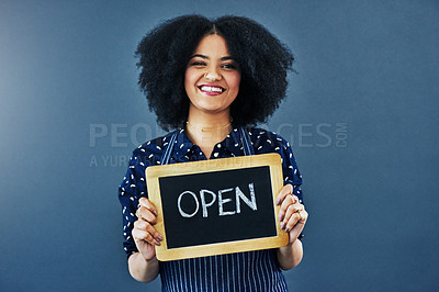 "Buy stock photo Studio shot of a young woman holding a chalkboard with the word ""open"" on it against a blue background"