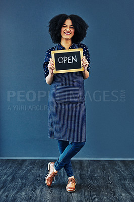 """Buy stock photo Studio shot of a young woman holding a chalkboard with the word """"open"""" on it against a blue background"""