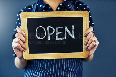 """Buy stock photo Cropped studio shot of a woman holding a chalkboard with the word """"open"""" on it against a blue background"""