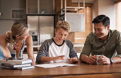 Buy stock photo Shot of parents helping their son with schoolwork at home