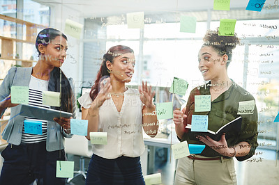Buy stock photo Shot of a group of businesswomen brainstorming on a glass wall in an office