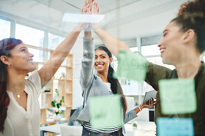 Buy stock photo Shot of a group of businesswomen high fiving in an office