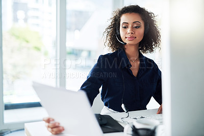 Buy stock photo Cropped shot of an attractive young female call center agent reading some paperwork while working in her office