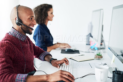 Buy stock photo Cropped shot of a handsome young male call center agent working in his office