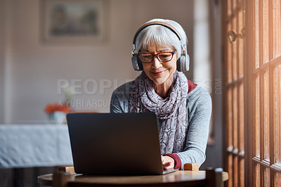 Buy stock photo Shot of a senior woman using a laptop and headphones in a retirement home