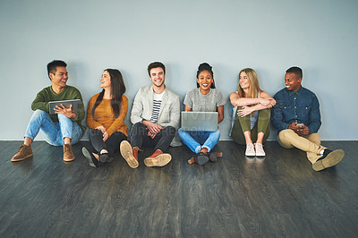 Buy stock photo Full length portrait of a group of young businesspeople using their wireless devices while sitting in a row in their office