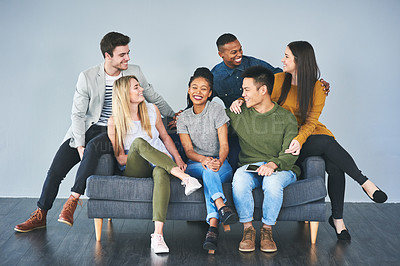 Buy stock photo Full length portrait of a group of young creative businesspeople sitting on a sofa in their office