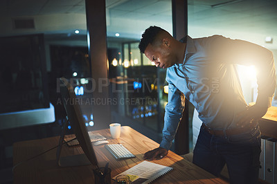 Buy stock photo Cropped shot of a handsome young businessman suffering with back pain while working late at night in a modern office