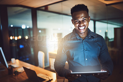 Buy stock photo Cropped portrait of a handsome young businessman using his tablet while working late at night in a modern office