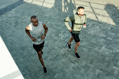 Buy stock photo High angle shot of two sporty men exercising together outdoors