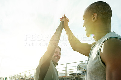 Buy stock photo Shot of two sporty men giving each other a high five while exercising outdoors
