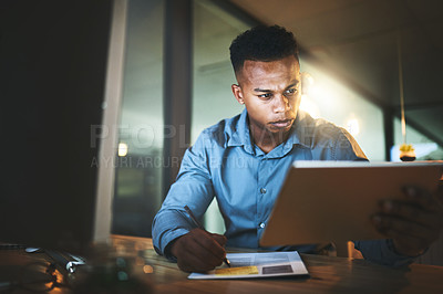 Buy stock photo Cropped shot of a handsome young businessman using his tablet while working late at night in a modern office