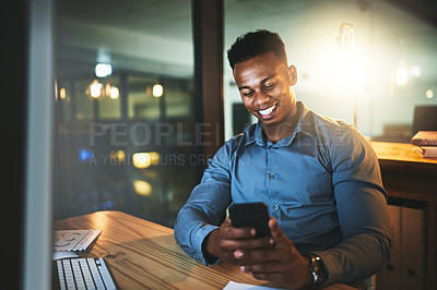 Buy stock photo Cropped shot of a handsome young businessman sending a text message while working late at night in a modern office