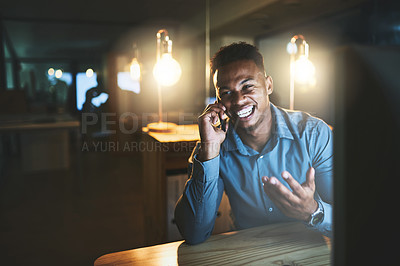 Buy stock photo Cropped shot of a handsome young businessman making a phonecall while working late at night in a modern office