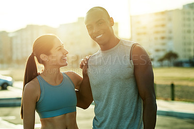 Buy stock photo Shot of a sporty young man and woman standing together outdoors