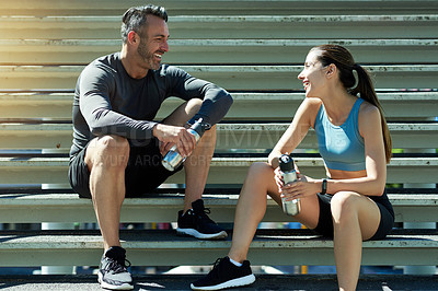 Buy stock photo Shot of a sporty couple taking a break while exercising outdoors
