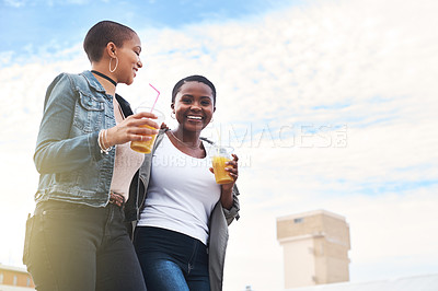 Buy stock photo Low angle shot of two young women walking in the city laughing while holding their cool drinks