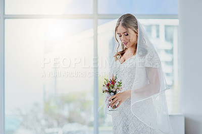 Buy stock photo Shot of a beautiful young bride holding a bunch of flowers on her wedding day