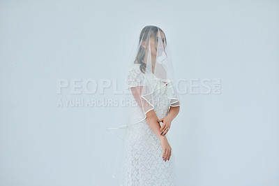 Buy stock photo Studio shot of a beautiful young bride on her wedding day against a gray background