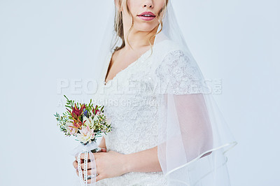 Buy stock photo Cropped studio shot of a beautiful bride holding a bunch of flowers on her wedding day against a gray background