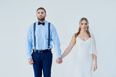 Buy stock photo Studio shot of a young couple holding hands on their wedding day against a gray background