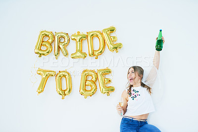 """Buy stock photo Studio shot of a happy young woman celebrating her engagement with """"bride to be"""" in balloons on the wall"""