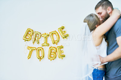 "Buy stock photo Studio shot of a happy young couple celebrating their engagement with ""bride to be"" in balloons on the wall"
