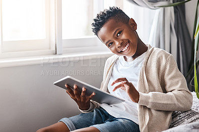 Buy stock photo Portrait of an adorable little boy using a digital tablet at home