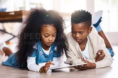 Buy stock photo Shot of two adorable little siblings using a digital tablet together at home