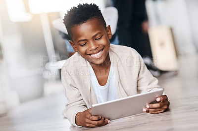 Buy stock photo Shot of an adorable little boy using a digital tablet at home