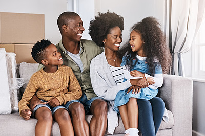 Buy stock photo Shot of a happy family sitting on a couch in their new home