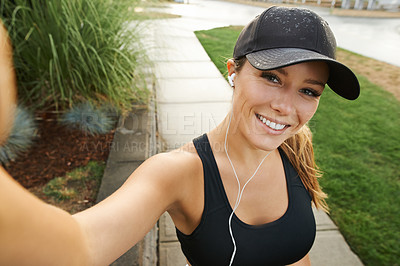 Buy stock photo Portrait of a sporty young woman taking selfies while exercising outdoors