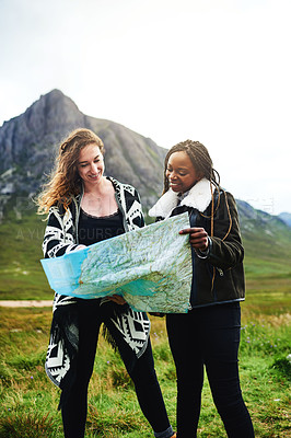 Buy stock photo Shot of two friends looking at a map while out exploring nature