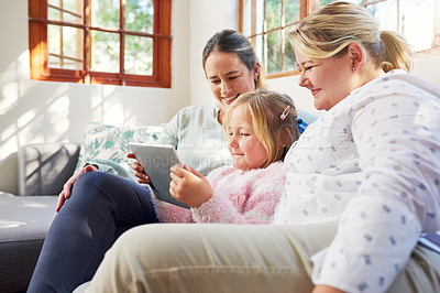 Buy stock photo Shot of a little girl using a digital tablet with her mothers at home