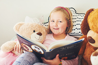 Buy stock photo Portrait of an adorable little girl reading a book with her teddy bears at home