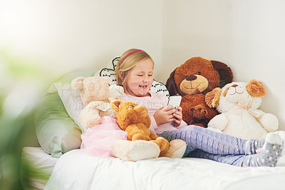 Buy stock photo Shot of an adorable little girl using a cellphone while lying on her bed at home