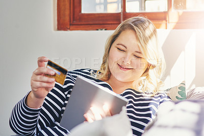 Buy stock photo Cropped shot of an attractive young woman using a tablet in her home