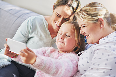Buy stock photo Shot of a family taking selfies together at home